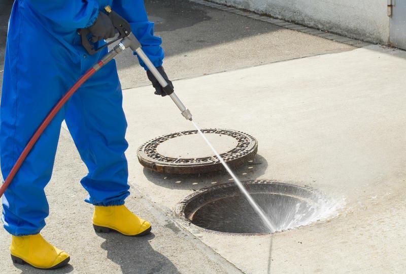 Процесс очистки канализационного колодца